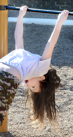 Kevin Harvison | Staff photo<br /> Aiyannah Young contorts her body as she sticks the landing after twirling around a bar on the Emerson playground.