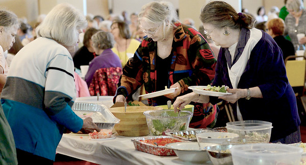 KEVIN HARVISON | Staff photo<br /> Ladies go through the salad line before the start of the 47th Annual Woman's Holy Week Luncheon at the Masonic Temple Thursday.