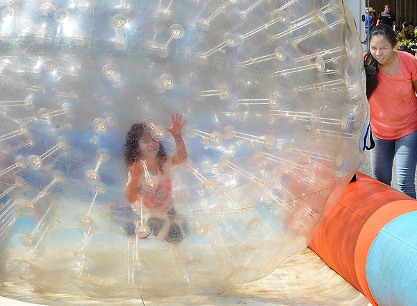 Kevin Harvison | Staff photo<br /> An unidentified girl rolls inside of a ball on Choctaw Avenue Saturday during the Culture Fest celebration in McAlester.