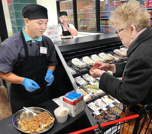 KEVIN HARVISON | Staff photo<br /> Linda Rodgers, right, of McAlester, gets a taste from a sample at the Pruitt's Grand Opening Monday.