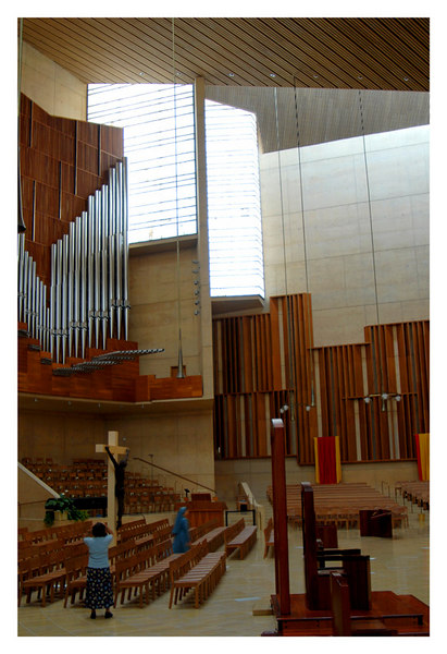 A view of the altar from the side with the ogan pipes showing. the bright lights are from the alabaster panels that diffuse direct sunlight potecting the expensive tapestries that hang all around the interior walls.