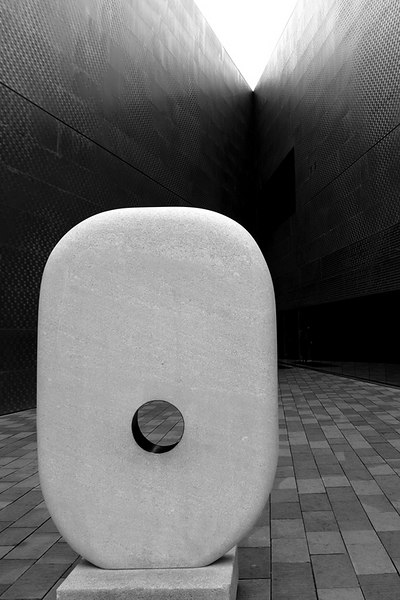 The monolith with a hole at the court by the cafeteria.