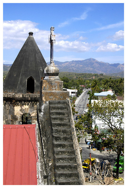 With the main bell tower as the point of view and looking at the secondary belltower and the town of Miagao.