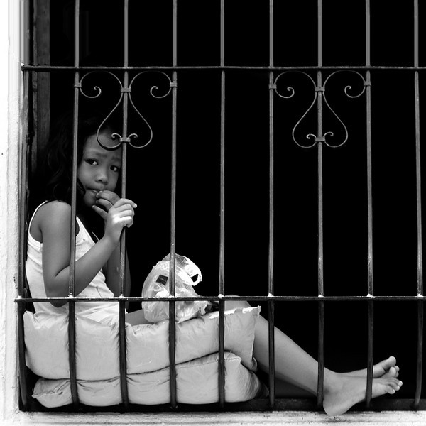 "I have to take a picture of this girl cooly relaxing in an old style security grille of their house. She is like saying, ""I am here, come take my picture."""