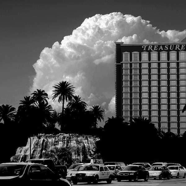 This is the Treasure Island Hotel and Casino Building and their erupting volcano and waterfall with a dramatic cloud formation at the background.