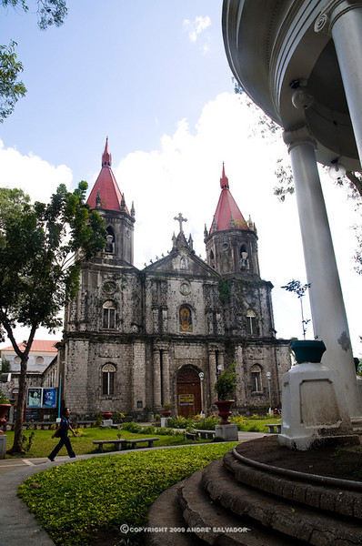 The two red spire roofs dominate the downtown skyline of of the small city of Molo. A domed band roof supported by colonnades is directly across after the landscaped front.