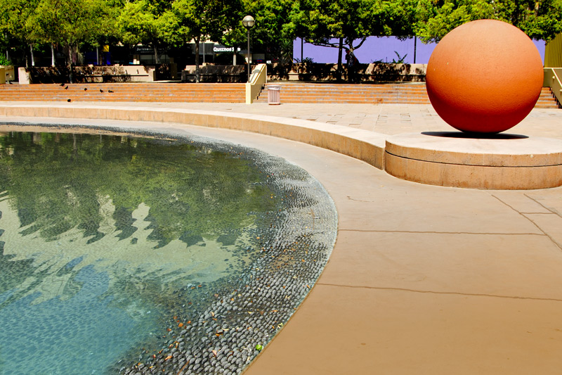 A view of the reflecting pool by the fountain and the huge red orange ball. It is one of several in the plaza.