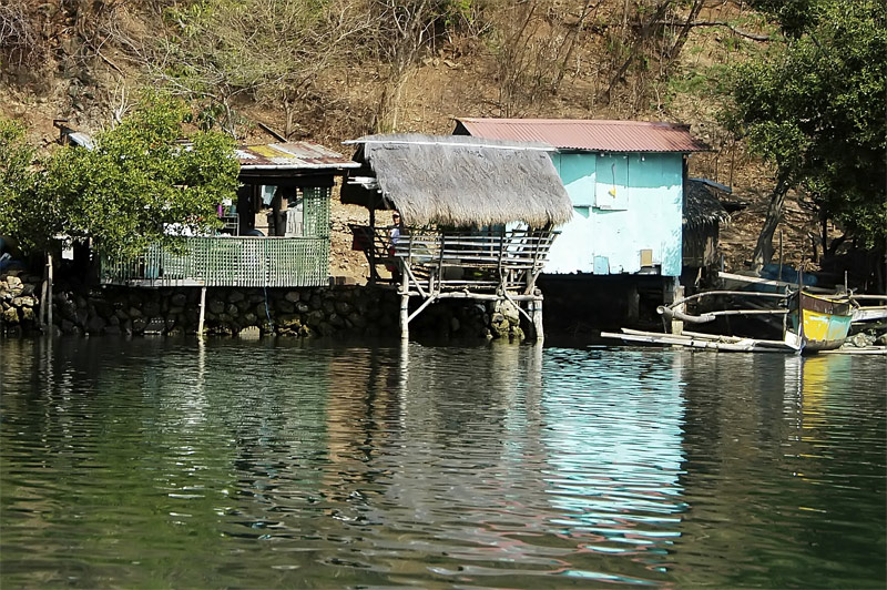 This fisherman's home is composed of three structures. The blue structure with the plywood siding is the sleeping area of the family. The structure at the center is their rest/living area. The structure on the left with green latticed wood siding is the kitchen and eating area. This was taken at Calyo River, Calayo, Batangas.