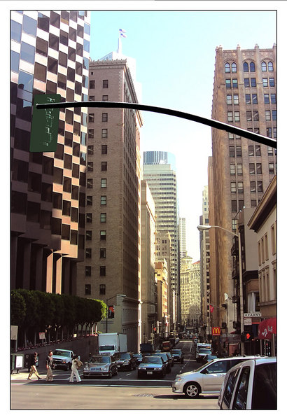 This is a view of downtown San Francisco. The traffic light you see at the foreground is at the corner of Kearny and Pine street. I am standing near the center of Pine Street. In this photo I am looking towards Market Street which is at a lower elevation than Market Street. Pine Street is one of those steep sloped streets in the city. Market Street is layed out diagonally on the gridiron street pattern