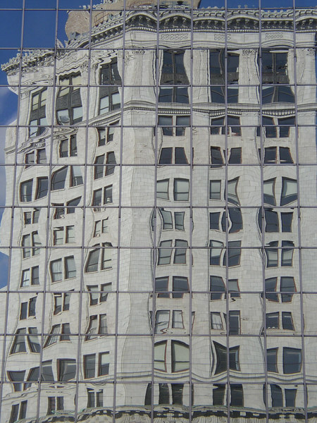A ONE HUNDRED YEAR OLD BUILDING REFLECTED AND DISTORTED BY A MODERN SKYSCRAPER