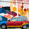 A painted old car against the background of a multi-colored wall.