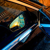 Luxury car mirror with sunset reflection