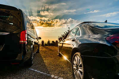 Two luxury cars facing to the colorful sunset, wide angle