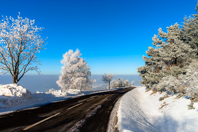Winter road in the mountains. Frozen trees and blue sky. Sunny day.Picturesque and gorgeous wintry scene.