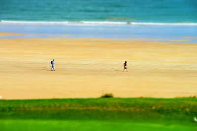 Two walkers on the beach miniature tilt shift view