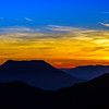 Idyllic sunset landscape with silhouettes of mountains and vivid colors