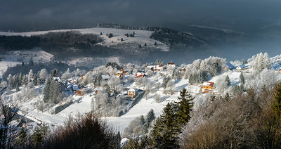 Aerial panoramic view of the little village in mountains. Winter with snow and frost. Picturesque and gorgeous wintry scene.