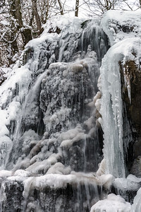 Beautiful icy waterfall in the forest. Vosges mountains.