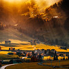 Sun beams lighting through the clouds and falling down to the little village on the hill, vivid colors of sunset, waves of green fields
