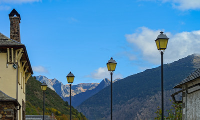 Line of yellow street lamps on mountains background