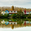 Old resort houses reflection in the lake water, freshness of autumn