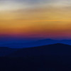 Sunset over the unending tuscany hills. Orange sky and blue silhouette of mountains