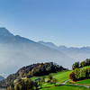 Farmland in Alps, green fields, cows, pasturage and high mountains on background, Switzerland