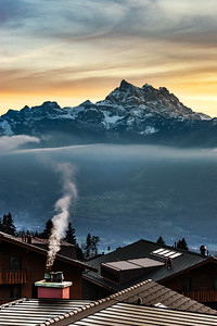 Smoke coming out of the chimney house on alpine mountains background