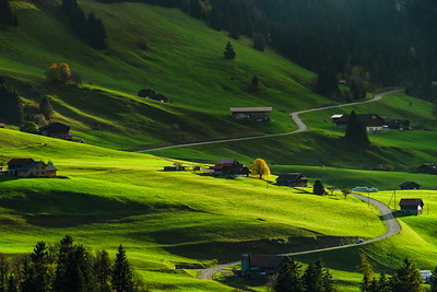 Beautiful hard shadows on green slope of alpine hill, swiss tuscany