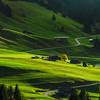 Beautiful hard shadows on green slope of alpine hill, swiss tuscany