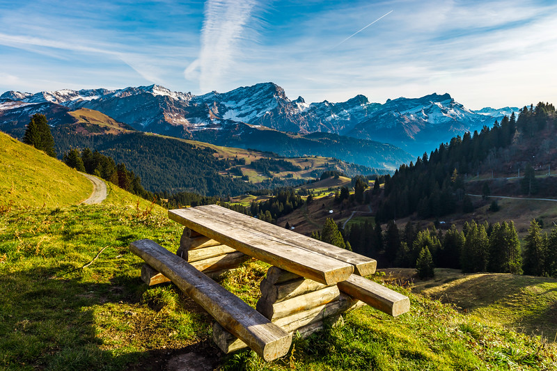 Natural wooden table with benches on the pederstrian path in Alps, landscape background