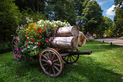 Flowering village in Alsace. Cart with logs decorated with flowers.