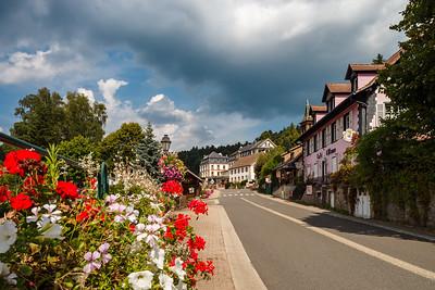 Flowering village in Alsace. Sunlit streets full of flowers.