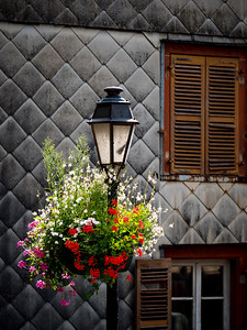 Flowering village in Alsace. Decoration of street lamps with potted flowers and plants.