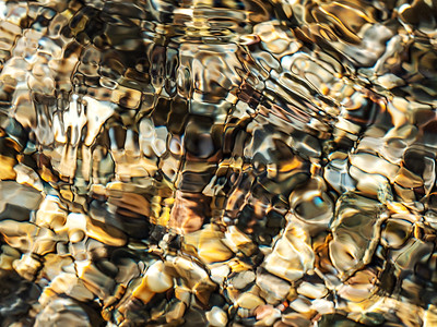 Background texture for relaxation. Stones at the bottom of a reservoir in sunlight. Amazing creations of nature.