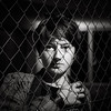 Portrait of a young girl through the bars. Restrictions and lack of freedom.