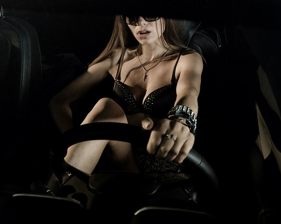 Sexy glamour girl sitting in a car