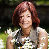Portrait of a beautiful woman with deep red hair in the garden against the background of nature and flowers.