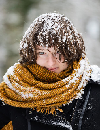 Young girl in a snowy forest. Plays with fresh snow. Snow falls from the trees directly on itself.