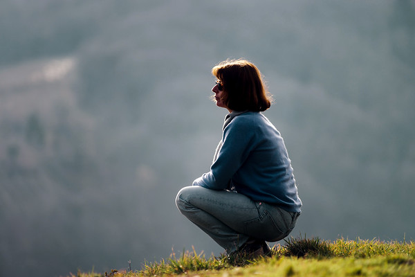 Woman silhouette. Sitting on the hill. Relaxation and tranquility.