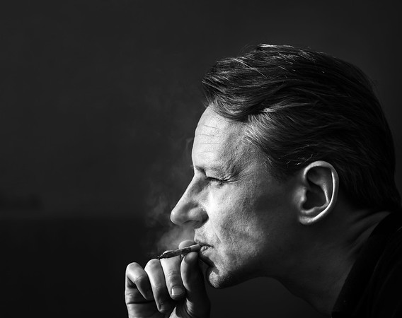 A man with a cigarette. Hard contrast of sunlight. Smoking and health.