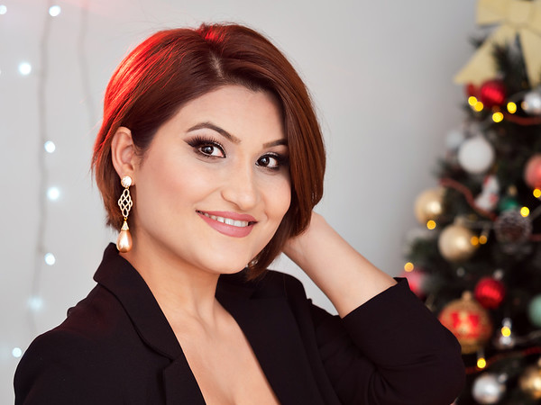 Christmas shooting. Beautiful model with New Year's gifts on background of a Christmas tree.