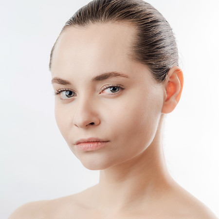Beautiful Young Woman with Clean Fresh Skin look away .Girl beauty face care. Facial treatment . Cosmetology , beauty and spa. Natural cosmetic product. Concept of Organic, Bio Cosmetics. Isolated on white background.