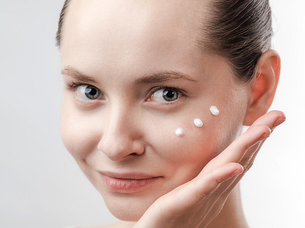 Beautiful Young Woman with Clean Fresh Skin. Drops of cream are applied on the cheek. Hand near the face. Girl beauty face care. Facial treatment . Cosmetology , beauty and spa. Natural cosmetic product. Concept of Organic, Bio Cosmetics. Isolated on white background.