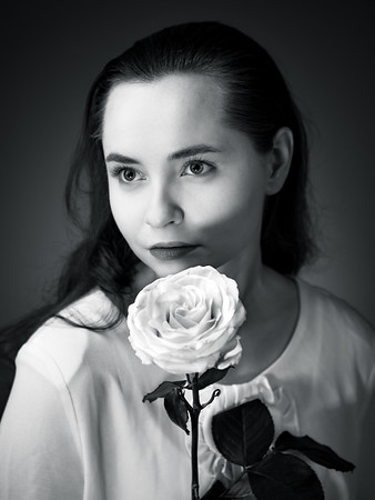 Studio portrait of a gentle young girl with a white rose. Bright colors and expressive eyes.