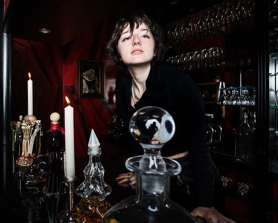 A young girl, dressed in a gothic style, poses in a posh alcoholic bar in red and black colors.