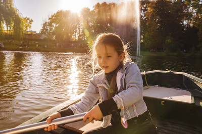 Little girl driving the boat on the pond