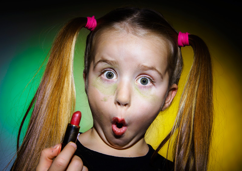 Funny little girl making make-up by herself