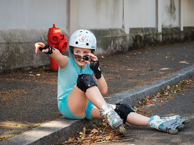 A schoolgirl is rollerblading in a helmet and protecting along the street. She was tired and sat down to rest.