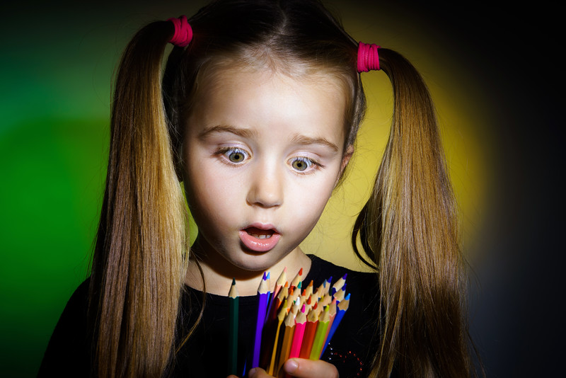 Cute little girl with colorful pencils